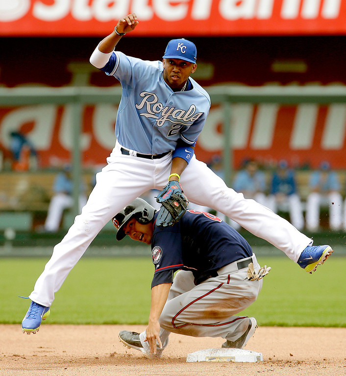 . Kansas City Royals shortstop Alcides Escobar (2) leaps over Minnesota Twins\' Kurt Suzuki after forcing him out at second during the fourth inning. (AP Photo/Charlie Riedel)
