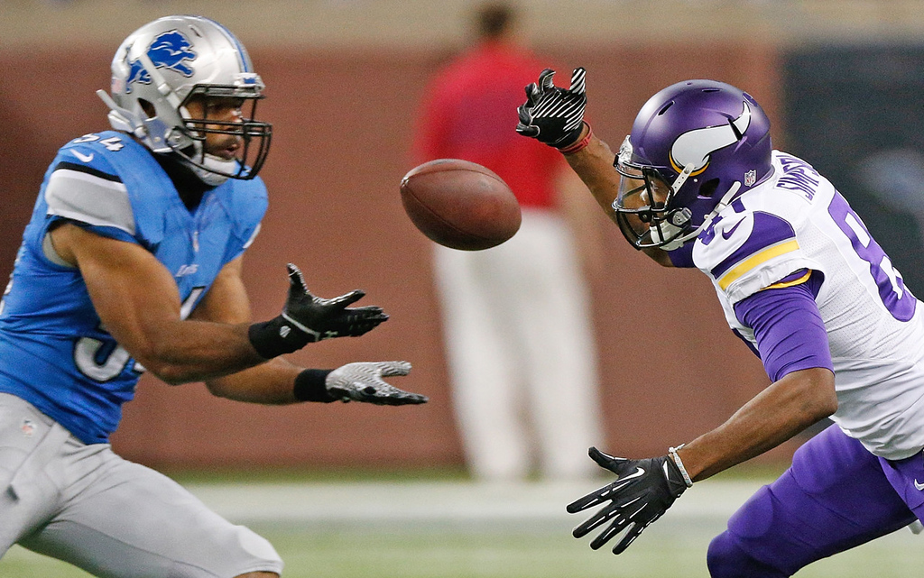 . Minnesota\'s Jerome Simpson, right, can\'t come up with a second-quarter pass as Detroit\'s DeAndre Levy intercepted the ball on the play. (Photo by Gregory Shamus/Getty Images)