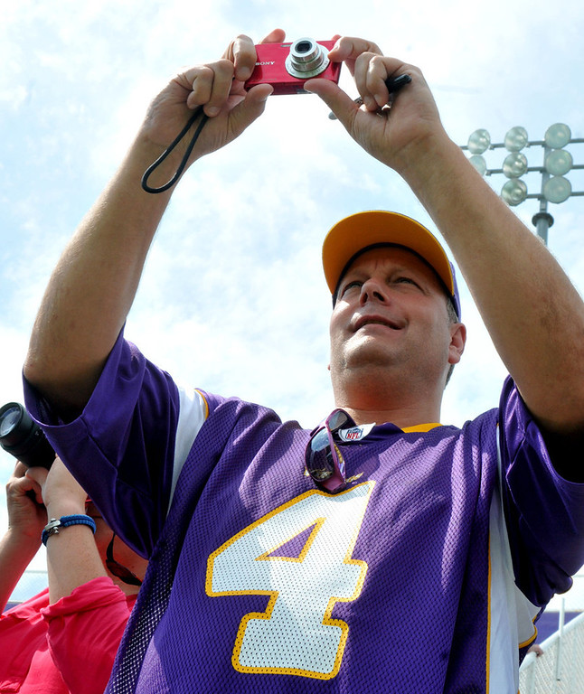 . In his vintage Brett Favre jersey, Harry Stadtler of Lakeville covers the action on the field from the stands with his point-and-shoot during the team\'s morning workout.   (Pioneer Press: John Doman)