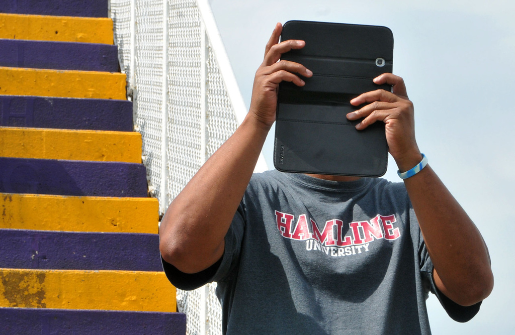 . Omar McMillan of Richfield uses his Samsung Galaxy tablet and phone to record the Vikings for posterity from the stands during the team\'s morning workout. (Pioneer Press: John Doman)