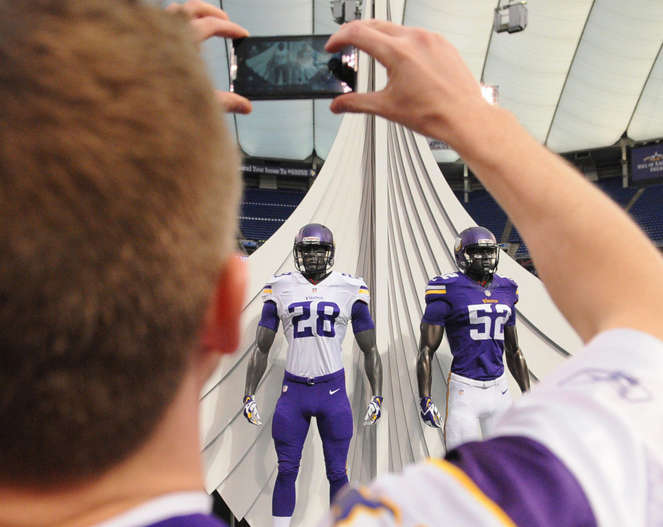 """. \""""I love \'em\"""" said Tom Lenhardt from Prior Lake as he takes a photo of the new Vikings uniforms. \""""I think they are simple and more traditional.\"""" (Pioneer Press: John Autey)"""
