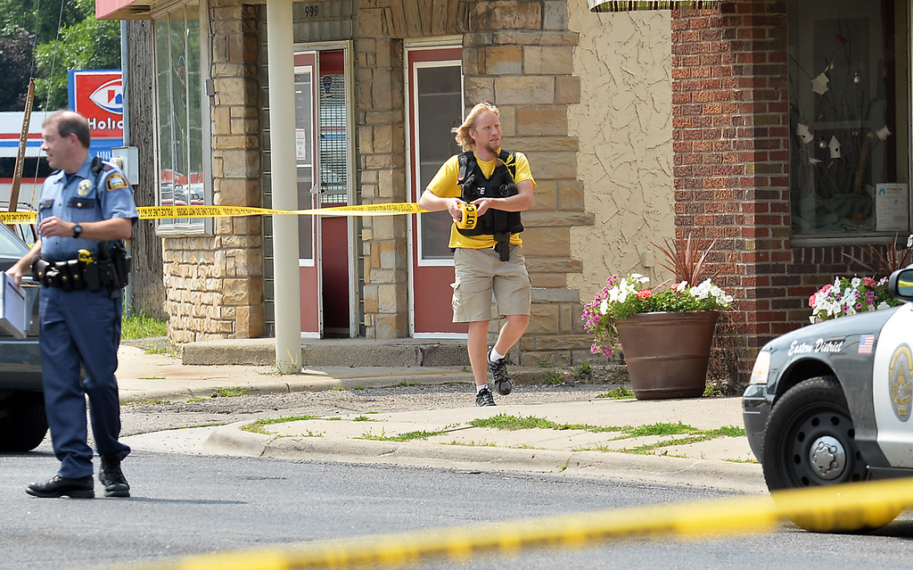 . A law enforcement officer ropes off a crime scene near the intersection of Smith Avenue and Dodd Road, where Mendota Heights Police Officer Scott Patrick was shot and killed on Wednesday. (Pioneer Press: Ben Garvin)