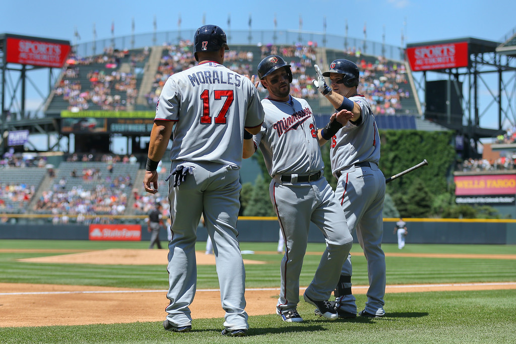 . Trevor Plouffe #24 of the Minnesota Twins and Kendrys Morales #17 celebrate with Josh Willingham #16 after they scored during the first inning against the Colorado Rockies. (Photo by Justin Edmonds/Getty Images)