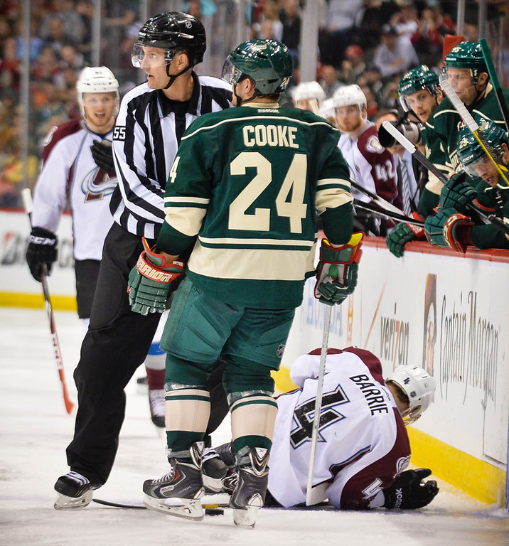 . A referee protects Minnesota\'s Matt Cooke from angry Colorado players moments after he kneed and injured Colorado defenseman Tyson Barrie, right, in the second period.  (Pioneer Press: Ben Garvin)