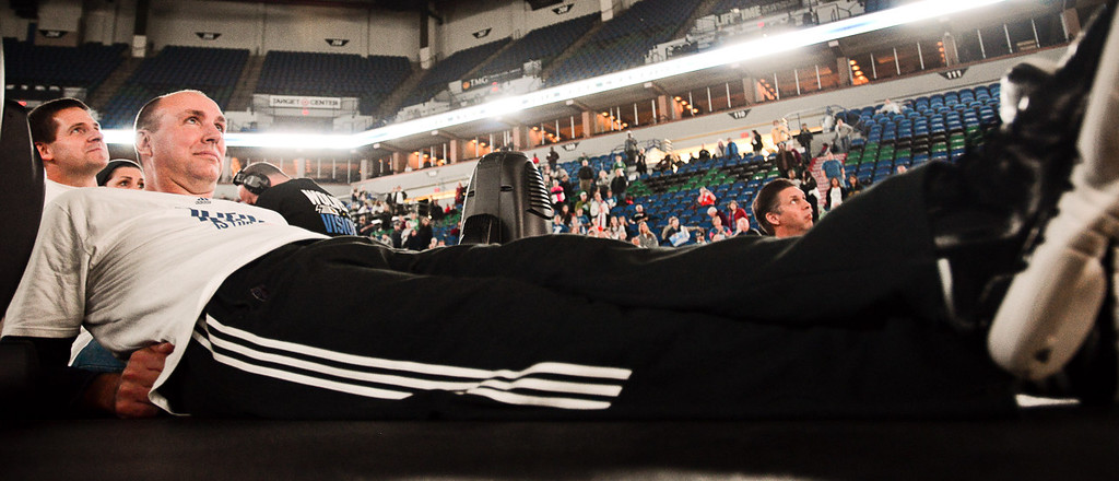 . Lynx assistant coach Jim Petersen stretches out on stage while watching a film about his team\'s season during the team\'s WNBA championship pep rally.