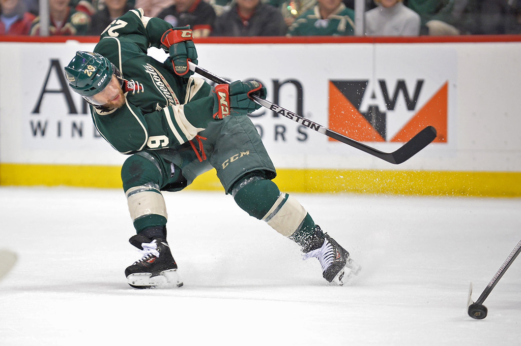 . Minnesota\'s Jason Pominville whacks the puck into the Blackhawks\' zone during the first period.  (Pioneer Press: Ben Garvin)