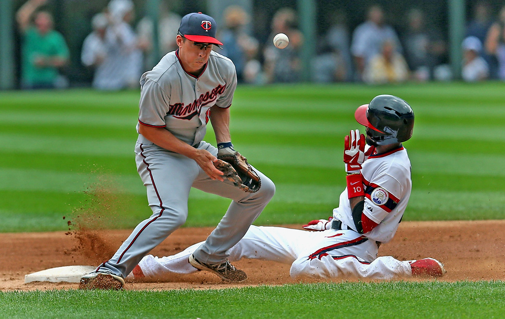 . Twins shortstop Doug Bernier bobbles the ball as White Sox base runner Alexei Ramirez  steals second base in the first inning. (Photo by Jonathan Daniel/Getty Images)
