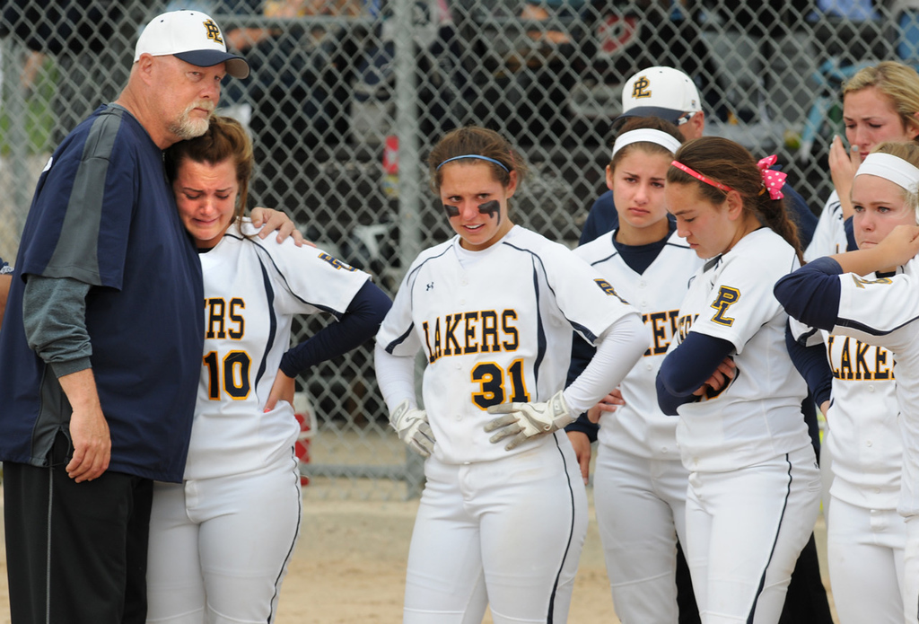 . Prior Lake assistant coach David Jelle, left, hugs outfielder Shannon Borchardt as her Lakers teammates cope with their 4-3 loss to Elk River. (Pioneer Press: Jean Pieri)