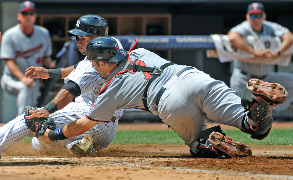 . New York\'s Zoilo Almonte is tagged out at home plate by Twins catcher Joe Mauer trying to score on Vernon Wells\' fly ball out to left fielder Clete Thomas in the third inning. (AP Photo/Kathy Kmonicek)