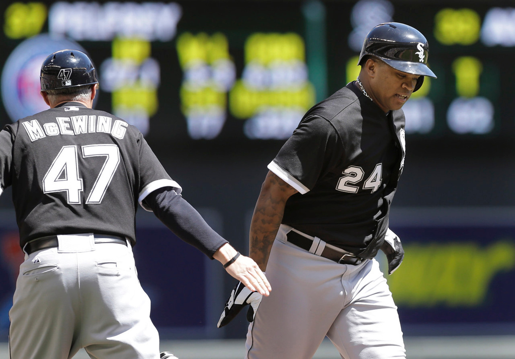 . Chicago\'s Dayan Viciedo, right, is congratulated by third base coach Joe McEwing after hitting a solo home run off  Twins starterr Mike Pelfrey in the fourth inning.  (AP Photo/Jim Mone)