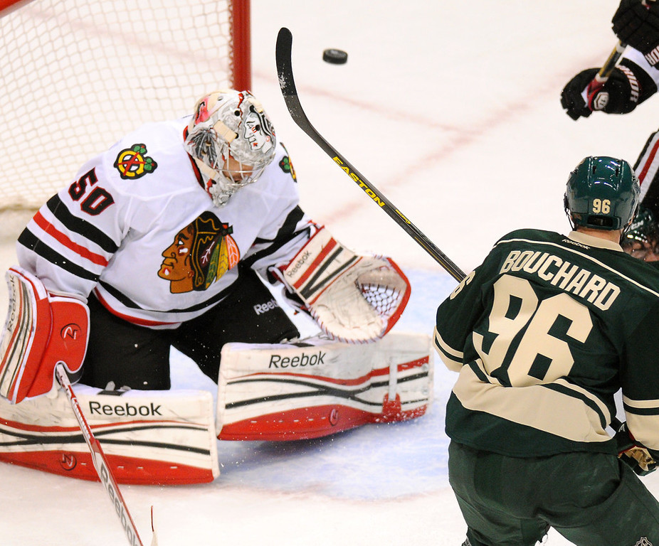 . Wild winger Pierre-Marc Bouchard, right, flips the puck past Chicago goalie Corey Crawford (50) for a tying goal in the first period. (Pioneer Press: John Autey)