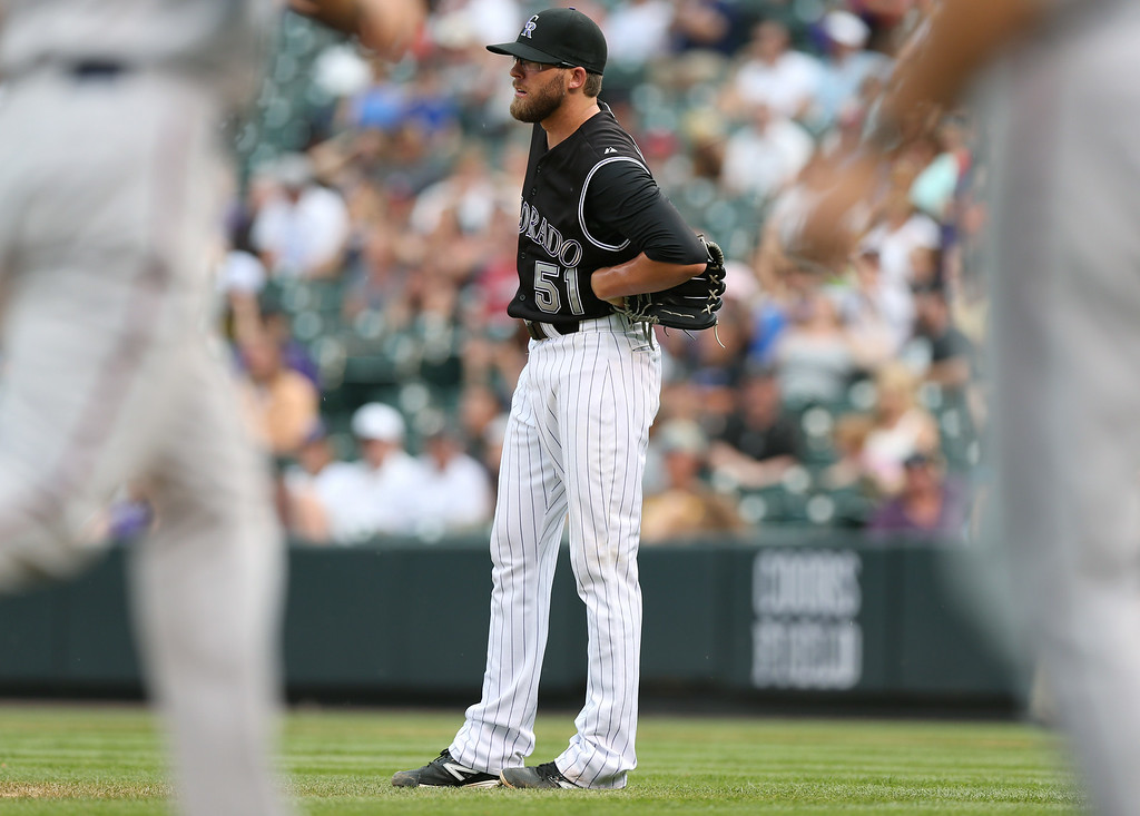 . Colorado Rockies relief pitcher Brooks Brown follows the flight of a three-run home run that he gave up to Minnesota Twins\' Brian Dozier in the ninth inning. (AP Photo/David Zalubowski)