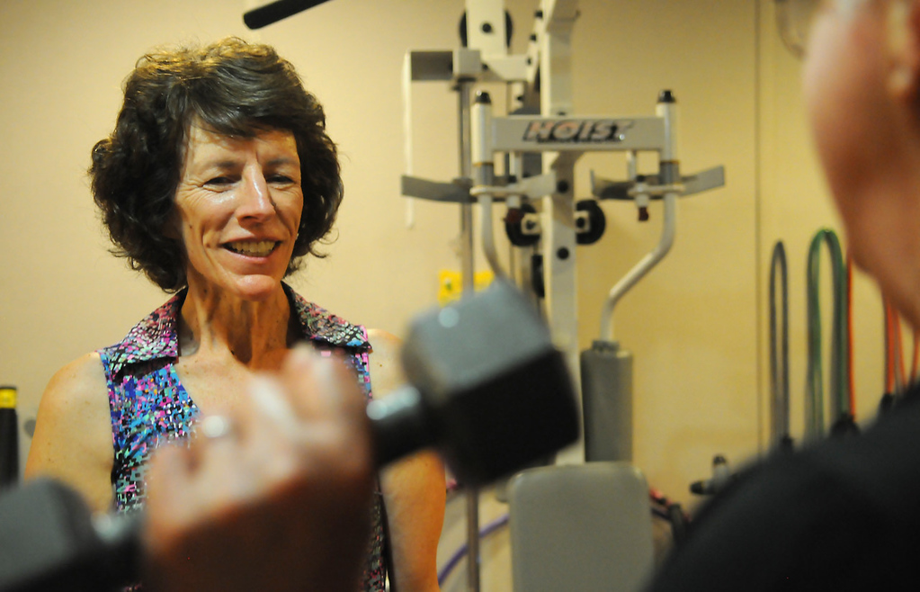 . Annie Elmer, left, watches as her client, Toni Lambert of St. Paul Park, works with hand weights. Since being diagnosed with HIV in 1990, Elmer works as a personal trainer, trying to help others stay healthy.   (Pioneer Press: John Autey)