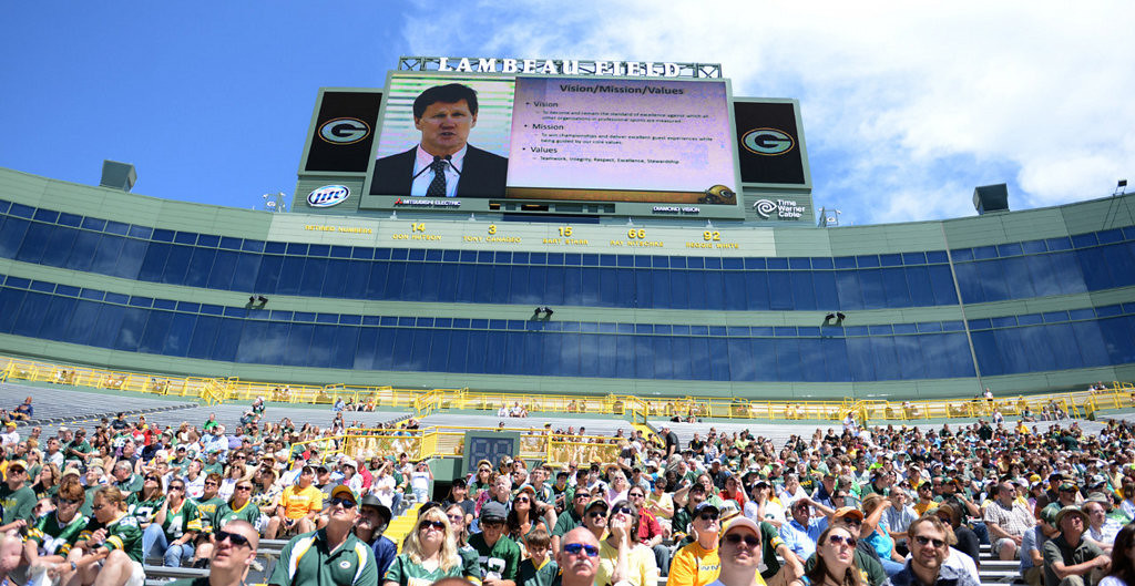 . Green Bay Packers fans and stockholders attend the team\'s annual shareholders meeting at Lambeau Field. The screen at top shows team president Mark Murphy. (AP Photo/The Green Bay Press-Gazette, H. Marc Larson)
