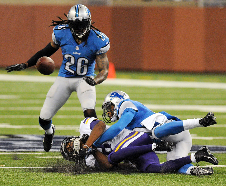 . Vikings wide receiver Jerome Simpson is brought to the ground by Lions cornerback Darius Slay, who was penalized for holding Simpson on the play in the second quarter. At left is Lions safety Louis Delmas. (Pioneer Press: Chris Polydoroff)