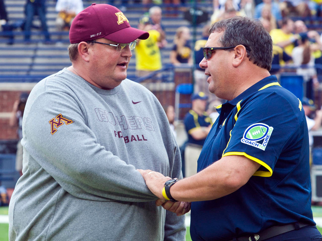 . Minnesota defensive coordinator and acting head coach Tracy Claeys, left, shakes hands with Michigan head coach Brady Hoke. Minnesota coach Jerry Kill has suffered another seizure and did not make the trip. (AP Photo/Tony Ding)