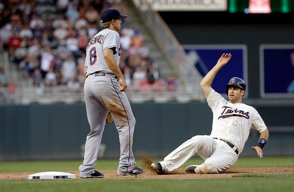 . Minnesota Twins\' Joe Mauer slides safely into third by Cleveland Indians third baseman Lonnie Chisenhall as he advanced from first on a single by Justin Morneau in the sixth inning. (AP Photo/Jim Mone)