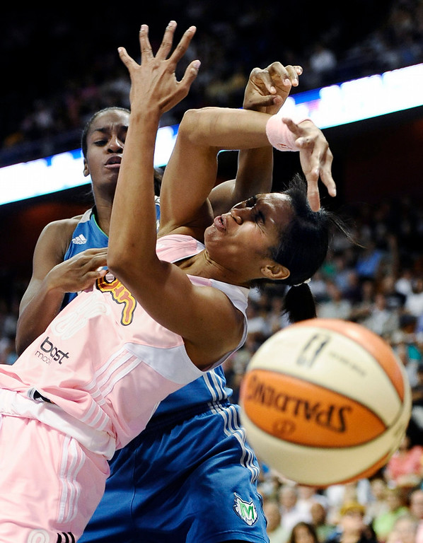 . Minnesota Lynx\'s Devereaux Peters, left, knocks the ball from Connecticut Sun\'s Iziane Castro Marques during the second half. (AP Photo/Jessica Hill)