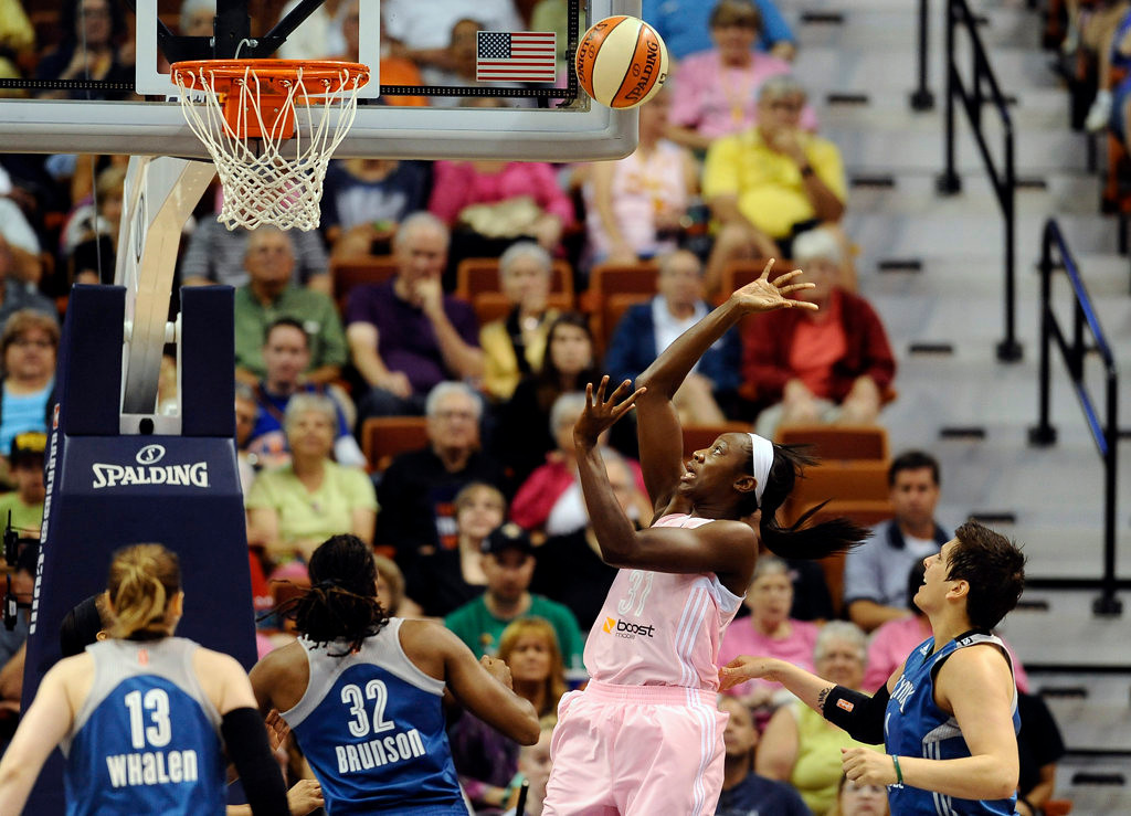 . Connecticut Sun\'s Tina Charles watches her shot as Minnesota Lynx\'s Lindsay Whalen, left, Rebekkah Brunson, second from left, and Janel McCarville, right, defend during the first half.  (AP Photo/Jessica Hill)