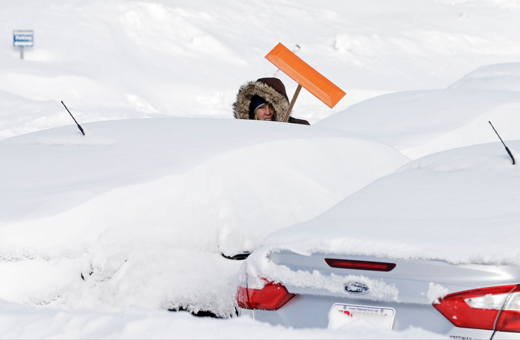 . Freeway Ford sales consultant Debra Anderson makes her way through the lot to clear snow off new cars Friday in Bloomington.  (Associated Press: Jim Mone)