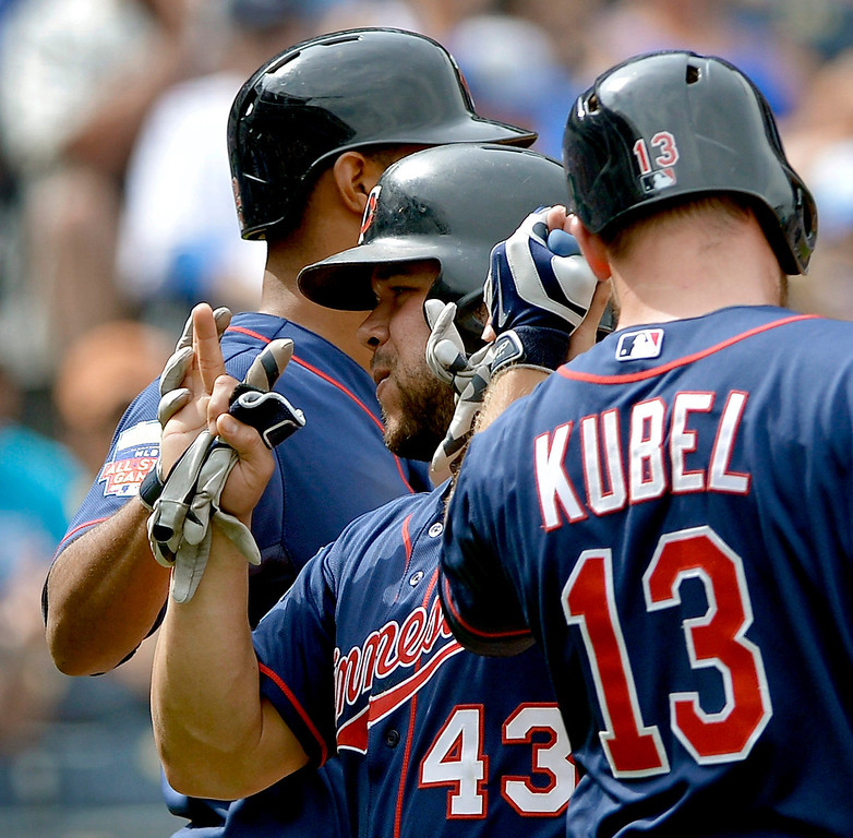 . The Minnesota Twins\' Josmil Pinto (43) is greeted by Aaron Hicks (32) and Jason Kubel (13) after scoring on a two-run double by Kurt Suzuki in the seventh inning. (John Sleezer/Kansas City Star/MCT)
