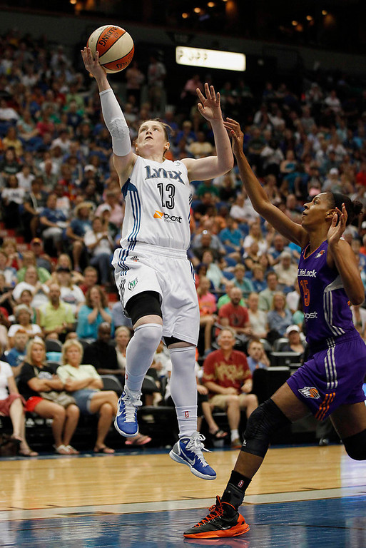 . Minnesota Lynx guard Lindsay Whalen (13) jumps up to the basket past Phoenix Mercury Briana Gilbreath (15) in the first half. Whalen scored 14 of her teams 91 points.(AP Photo/Stacy Bengs)