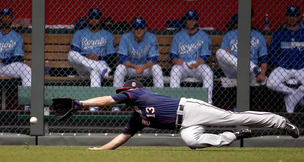 . Minnesota Twins\' Jason Kubel dives for a double hit by Kansas City Royals\' Justin Maxwell during the second inning. (AP Photo/Charlie Riedel)