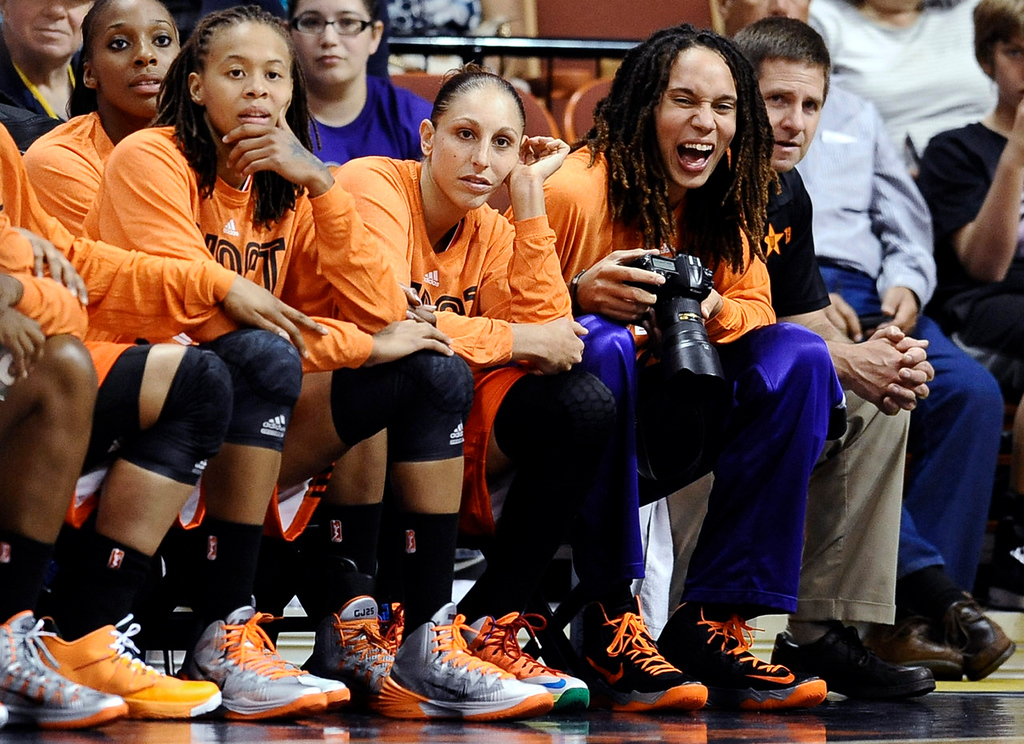 . West\'s Brittney Griner, right, of the Phoenix Mercury, laughs while taking photographs as teammates Seimone Augustus, left, of the Minnesota Lynx, and Diana Taurasi, of the Mercury, watch play during the second half. (AP Photo/Jessica Hill)