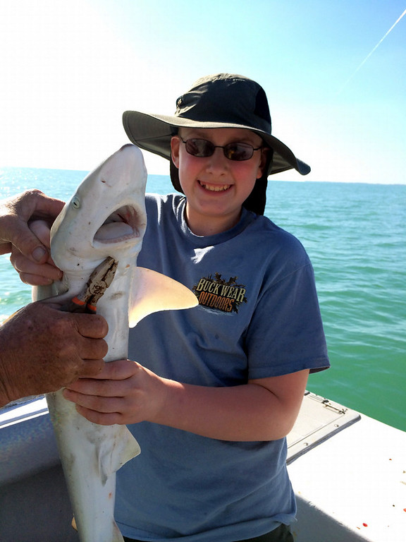 """. Sean O\'Neill, 12, holds up a black nose shark that he caught and released while fishing with his mom, Penny O\'Neill, in the Gulf of Mexico near Fort Myers, Fla., in March.  Mom reports: \""""In addition to getting MLB player autographs at the Twins\' Spring Training 2014, Sean fulfilled his spring break goal of catching a shark.\"""" Helping Sean hold the fish is Captain Brad.(Photo courtesy of Penny O\'Neill)"""