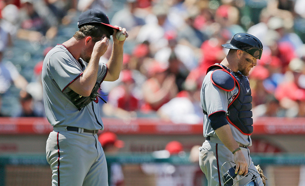 . Twins starter Mike Pelfrey, left, wipes his face while talking with catcher Ryan Doumit during the sixth inning against the Angels. Pelfrey gave up just one run on five hits during his six innings of work.   (AP Photo/Jae C. Hong)