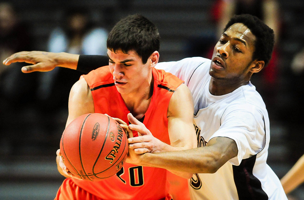 . St. Paul Johnson\'s Quashingm Smith-Pugh reaches around to knock the ball loose for a turnover from Delano\'s Zach Checkal in the first half. (Pioneer Press: Ben Garvin)