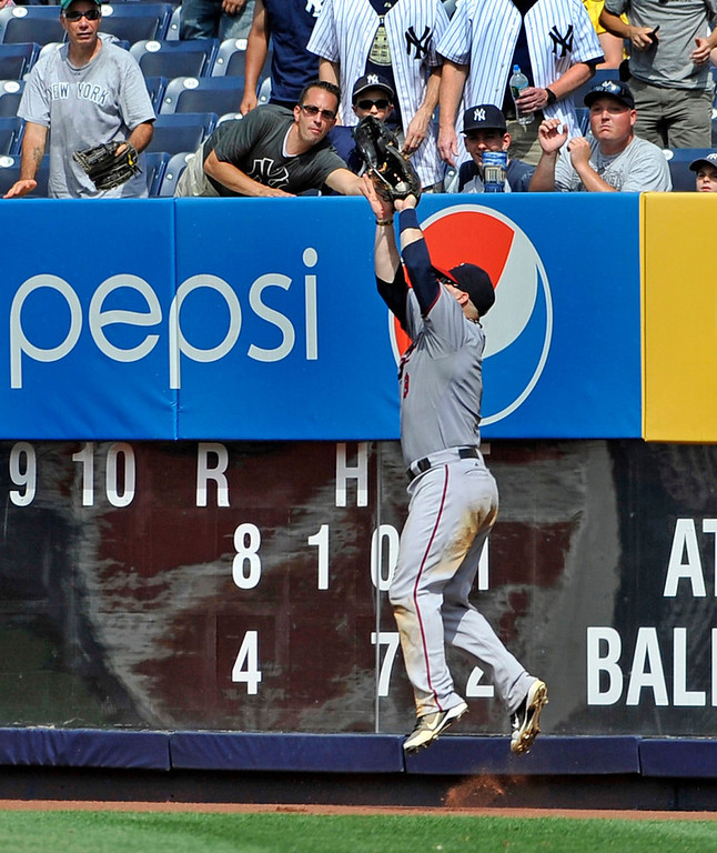 . Twins right fielder Ryan Doumit leaps at the outfield wall to rob New York\'s Zoilo Almonte of a home run in the seventh inning. (AP Photo/Kathy Kmonicek)