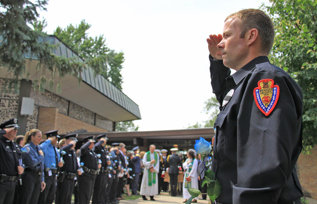 . A Mendota Heights firefighter salutes as officer Scott Patrick\'s casket is carried out of St. Stephen\'s Lutheran Church following his service in West St. Paul on Wednesday.  (Minnesota Department of Public Safety Pool Photo: Jen Longaecker)