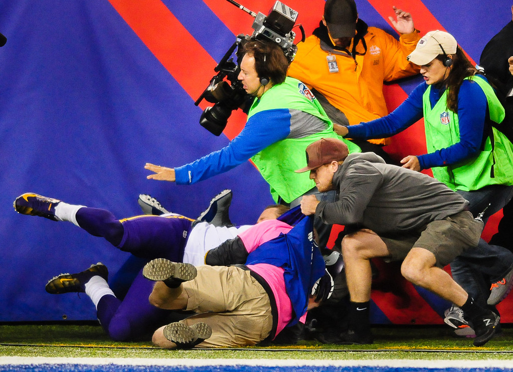 . Vikings cornerback Xavier Rhodes plows into a group of photographers in the end zone during the third quarter against the Giants. (Pioneer Press: Ben Garvin)