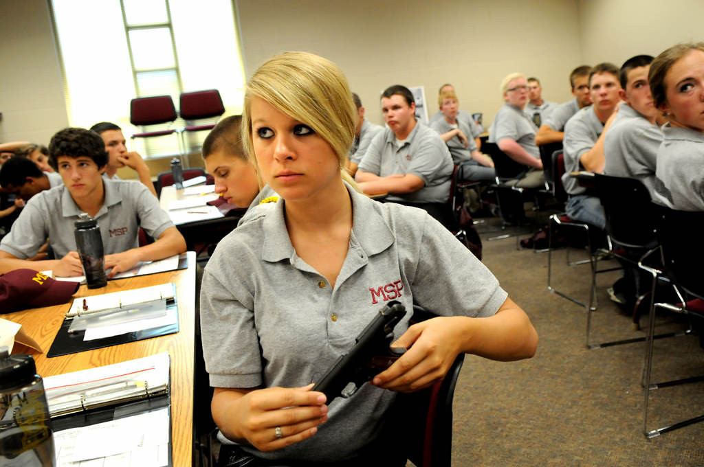 """. Macy Hennen, 16, from Pierz, Minn., listens to a Minnesota State Patrol sergeant talk about different kinds of guns during a Minnesota State Patrol High School Summer Camp at Camp Ripley, near Little Falls. The sergeant had the cadets pass around the unloaded guns. Hennen said she is \""""here for the experience. To see if I\'m interested.\"""" (Pioneer Press: Jean Pieri)"""