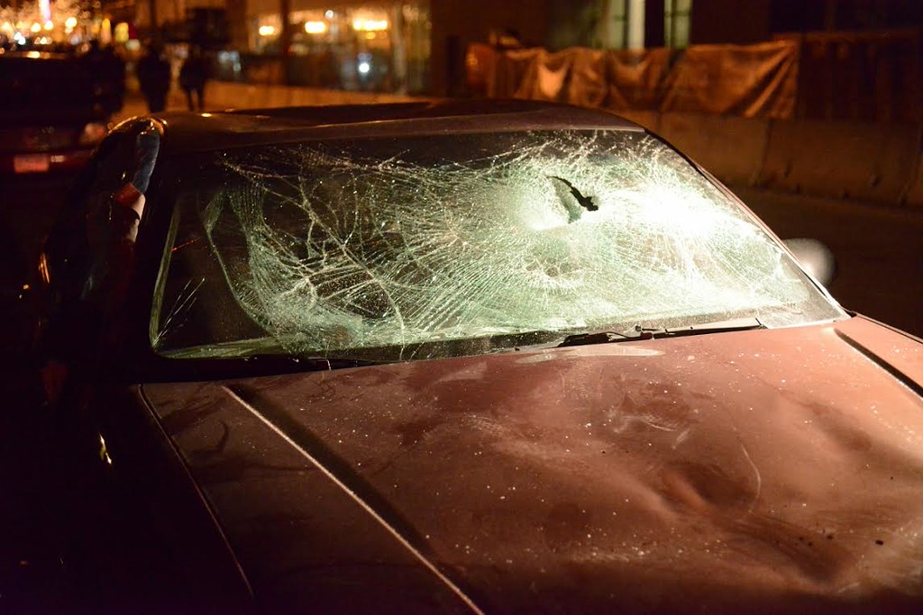 . A car sits damaged in Minneapolis\' Dinkytown after hockey fans filled the streets Saturday after the Gophers\' loss in the Frozen Four. (Pioneer Press: C.J. Sinner)