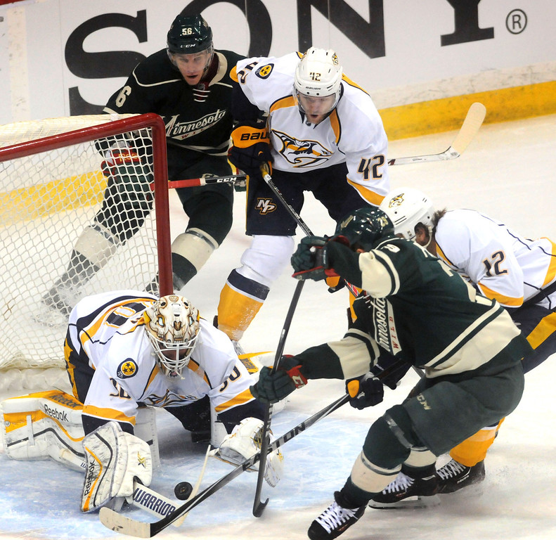 . The Wild\'s Erik Haula, behind the net,  scored in the second attempt on this play by Jason Pominville  in the first period.  Clockwise from rear:  Haula, Nashville\'s Mattias Ekholm and Mike Fisher, the Wild\'s Pominville and Nashville goalie Carter Hutton.  (Pioneer Press: Scott Takushi)