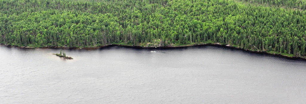 . A pair of paddlers (to the right of the small island) paddles the shoreline of a a lake inside Woodland Caribou Provincial Park in Ontario July 6, 2013. From the view of an aircraft, one can appreciate both the insignificance of people in a wilderness, as well as the achievement of traveling miles and miles powered only by muscle.