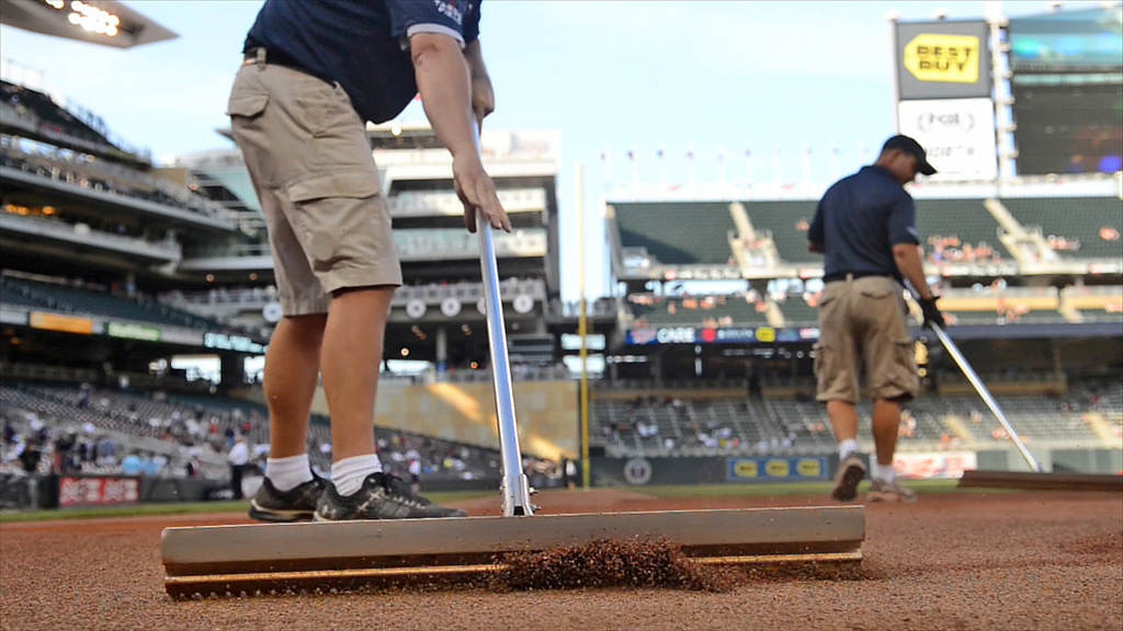 . Grounds crew staff smooth the sand around home plate with rakes before game time against the Yankees. (Pioneer Press: John Autey)