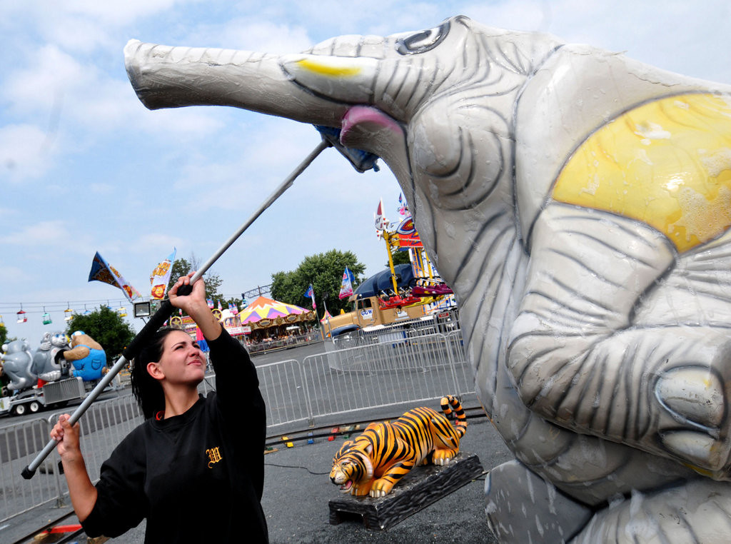. Kirsten Kreyfelt from Johannesburg, South Africa cleans an elephant-like locomotive engine, part the Safari Train located in Kiddieland at Minnesota State Fairgrounds, in St. Paul on Monday, August 19, 2013.  Preparations are underway  for the opening day of the 154th Minnesota State Fair which opens Thursday. (Pioneer Press: John Doman).