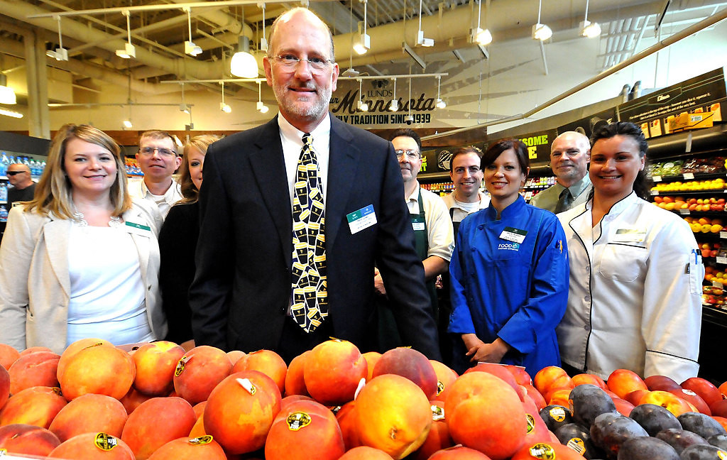. Tres Lund, pictured with employees this month at the Lunds store at 12th Street and Hennepin Avenue in Minneapolis, plans to open a new Lunds in downtown St. Paul. The urban grocery store is expected to function much like the location in downtown Minneapolis. (Pioneer Press: John Doman)