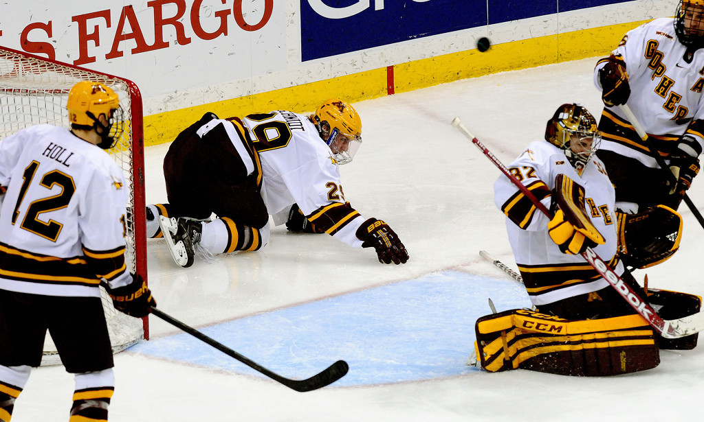 . Minnesota goaltender Adam Wilcox (32) deflects a puck as teammate Nate Schmidt (29) slides into the goal during the third period of  WCHA Final Five semifinal at the Xcel Energy Center Arena on Friday, March 22, 2013. (Pioneer Press: Sherri LaRose-Chiglo)
