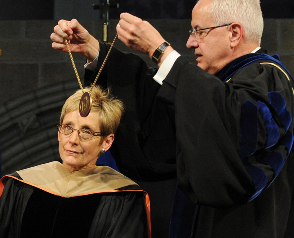 . Dr. Julie Sullivan readies herself as her predecessor, the Rev. Dennis Dease, right, places the presidential medallion around her neck during her inauguration as the new president of the University of St. Thomas. (Pioneer Press: Chris Polydoroff)
