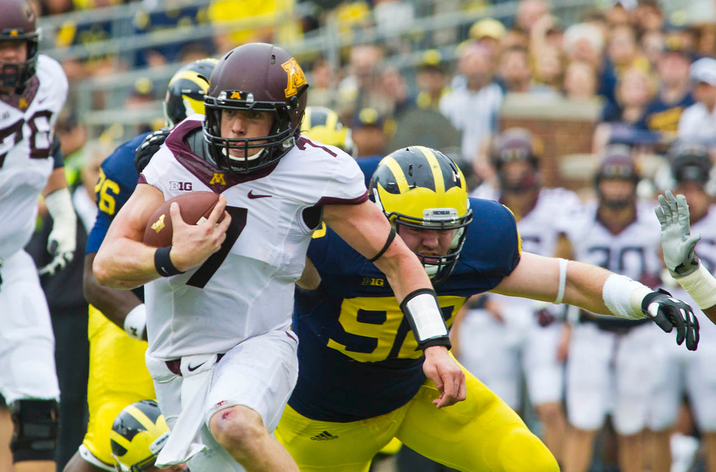 . Minnesota quarterback Mitch Leidner tries to break a tackle from Michigan defensive end Keith Heitzman in the first quarter. (AP Photo/Tony Ding)