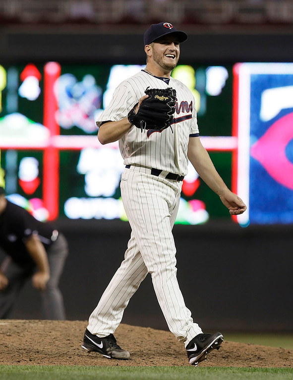 . Minnesota Twins pitcher Glen Perkins smiles toward plate umpire Gary Darling when he thought he had thrown a strike instead of a ball in the ninth inning. (AP Photo/Jim Mone)