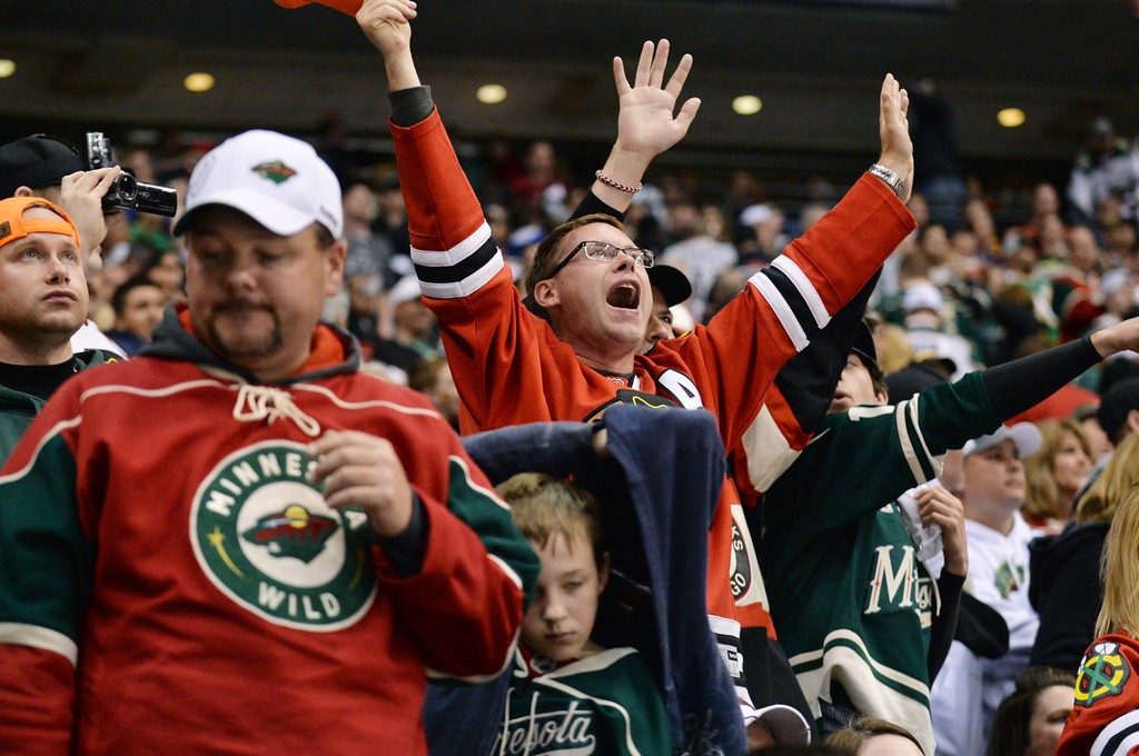 . Dejected Minnesota fans make their way to the exits as a Blackhawks fan celebrates after Chicago beat the Wild in overtime, 2-1, in Game 6. (Pioneer Press: Ben Garvin)