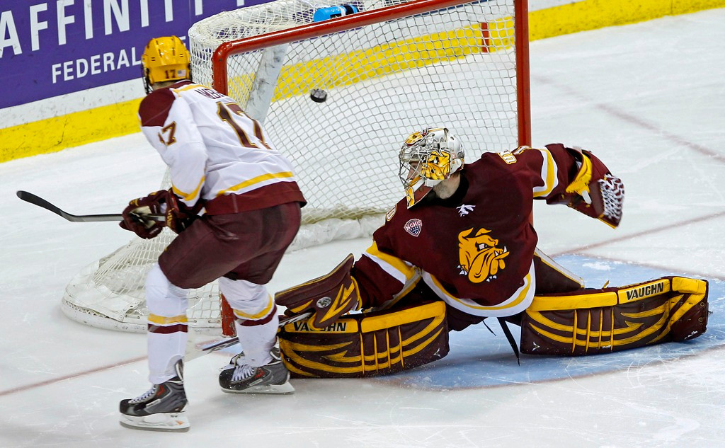 . Minnesota right winger Seth Ambroz, left, flips the game-winning goal past Minnesota Duluth goalie Aaron Crandall, right, in a shootout to decide the Gophers\' 5-4 win. (AP Photo/Ann Heisenfelt)