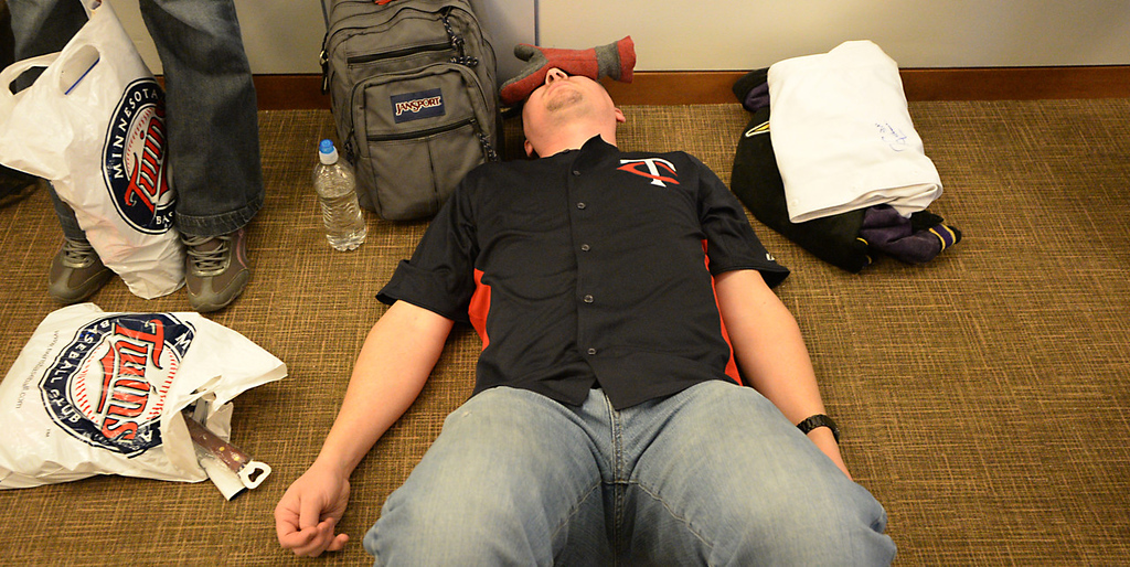 . A tired Jon Kragness, from Minneapolis, rest his eyes while in line to get Twins prospected Byron Buxton\'s autograph at Twinsfest at Target Field, Saturday, January 25, 2014(Pioneer Press: John Autey)