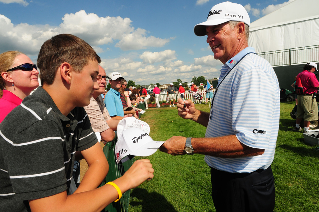 . Jay Haas signed the hat of Grant Schmitt, 14, of Elk River, left, on the final day of the 3M Championship. (Pioneer Press: Scott Takushi)