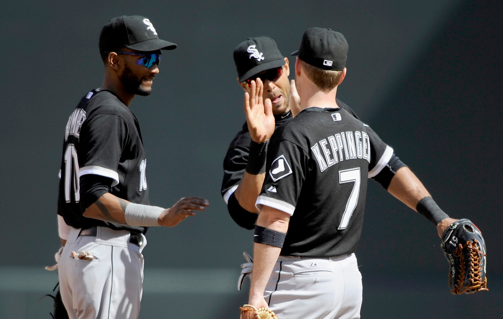 . White Sox players (from left) Alexei Ramirez, Alex Rios, and Jeff Keppinger celebrate Chicago\'s 9-4 win over the Twins on Wednesday. (Photo by Hannah Foslien/Getty Images)